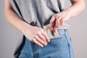 Person pocketing money that they collected.