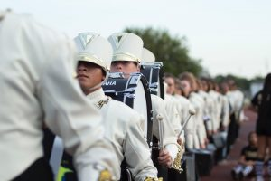 Marching Band procession in uniform with instruments.
