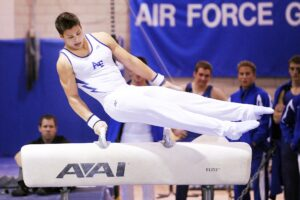 Male gymnast competing in the Pommel Horse routine.