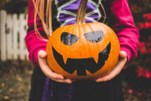 Kid holding a painted halloween pumpkin after attending a booster club fundraiser.